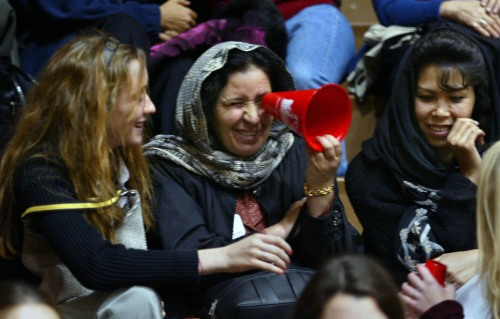 Afghan women attend a University of Nebraska Omaha volleyball game.  (l-r) Emily Dixon ,14, trys to tell Raahilah Mahmoodzaadah that her megaphone is not a spy glass.  Masoomah Beenish looks on.  (Omaha World-Herald photo by Bill Batson, used by permission)