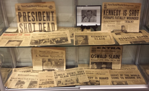 The Cronkite Gallery at Arizona State features a collection of newspapers covering the Kennedy assassination, with a photo of Cronkite removing his glasses to read the news of JFK's death.