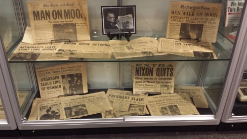 In the days before computer simulations, Cronkite used models to show what was happening in space, as in this photo surrounded in the Cronkite Gallery by front pages about space exploration.