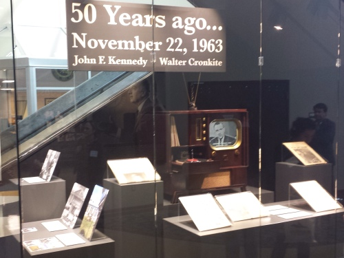 A Kennedy display at the Walter Cronkite Memorial in St. Joseph, Mo., includes a period TV set, playing video of Cronkite's coverage of the Kennedy assassination and funeral, with newspapers and photos relating to assassination coverage.