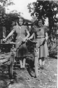 I asked Mary Lou if she might have a photo of Minda as a girl on her bike. She's on the right here, but certainly older than when she had the paper route. The woman on the left is not identified on the back of the photo.