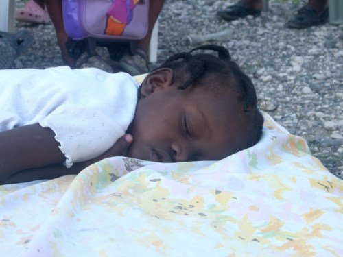 Maya sleeping on the ground after Robin Roberts and a GMA crew found her in Haiti in 2010.